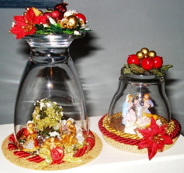 Mini presepi collocati sotto bicchieri di vetro.