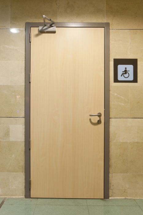 Puerta siguiendo el mismo acabado que el laminado de la pared, y con  herrajes de acero inoxidable.