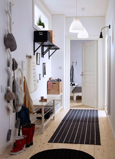 Vestíbulo pequeño con dos bancos zapateros, un espejo y tres colgadores con forma de árbol para chaquetas y bolsos, todo en blanco.