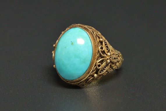 Vtg China Turquoise Ring Gold Vermeil Sterling Export Ring Offered here is a gorgeous vintage China export, Vermeil silver filigree ring with a exquisite, fine quality Sky Blue Turquoise specimen. The filigree design accents is that of butterflies & braided filigree. Wonderful condition with very little wear to the vermeil gold finish. The turquoise has a high polish with faint, russet matrix. A very fine piece! Adjustable size band but is currently a size 7. Marked Silver. Band measures ...