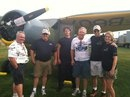 "Featured plane of the day at ""Cavanaugh Corner"" is the 1944 Stinson AT-19 Reliant Mk. 1. Tom Bullion (owner) is pictured with the CFM Crew and Rick Siegfried, President of Warbirds of America."