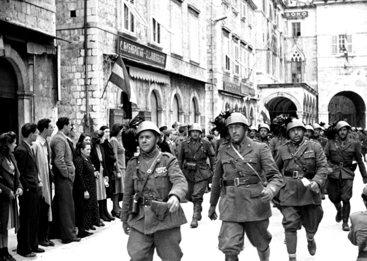"Italian Bersaglieri (""marksmen"") march through Dubrovnik as crowds watch on following the Axis invasion of Yugoslavia. The invasion ended when an armistice was signed on April 17, 1941, based on the unconditional surrender of the Royal Yugoslav Army, which came into effect at noon on April 18. Yugoslavia was then occupied and partitioned by the Axis powers."