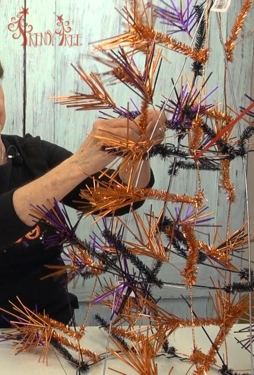 Needle Burst garland applied to a tomato cage, attach Deco Poly Mesh for a Halloween tree. Tutorial at Trendy Tree