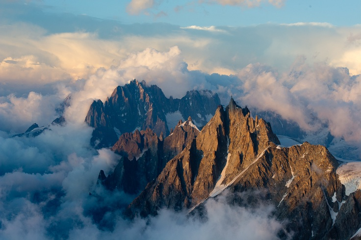 The magnificent Aiguille du Midi in late afternoon sun as seen from the summit of Aiguille Gouter during Summer traverse of Mont Blanc in Chamonix, France