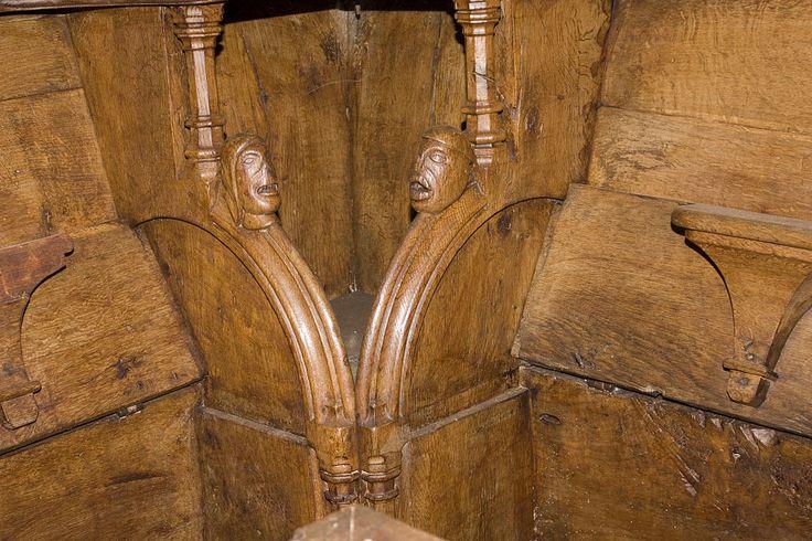 Église Saint-Martin (Prieuré d'Ambierle)— Moine et moniale dans l'encoignure des stalles.- LES STALLES, 4)  30 sièges sur 36 portent des numéros; les autres, à l'O. (côté nef) étaient réservés aux dignitaires et sont beaucoup plus larges. Devant la stalle 19, et dans une moindre mesure devant la 18 et la 20, la dalle au sol est usée de façon conséquente; l'accoudoir de cette stalle est aussi chanfreiné de façon anormale.
