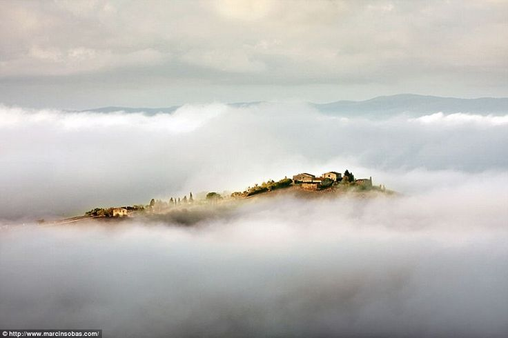 A Tuscan hillside is surrounded by clouds and mist while the distant shapes of mountains b...