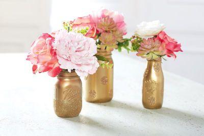 Centre de table floral dans des bocaux à lait dorés