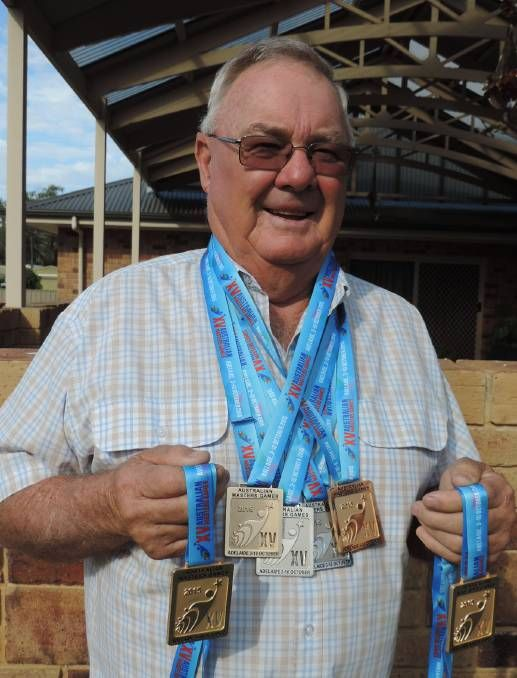 CHAMPION: Bob Andrews gathers his medals won at the Australian Masters games.