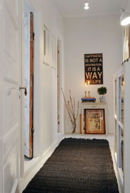 wąski przedpokój,biały przedpokój,korytarz,jak urzadzić wąski korytarz,biale ściany,skandynawski styl,nowoczesne mieszkanie,dekoracja holu,dekoracje do przedpokoju,typografie,czarny chodnik,dywan w przedpokoju,biała podłoga - Lovingit.pl