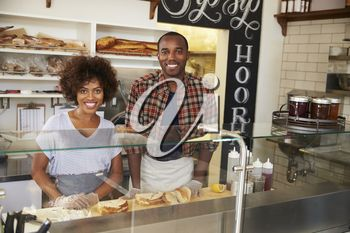 Black couple waiting behind the counter at a sandwich bar
