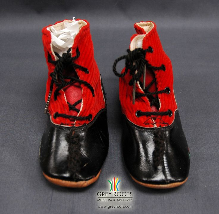 A pair of red corduroy and black leather child's boots. The soles of the boots are made of brown leather. Grey Roots Museum & Archives Collecion.