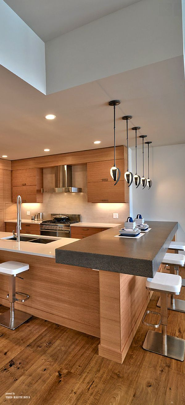 Clean lines. warm wood. no cabinet pulls. dark and light stone countertops.