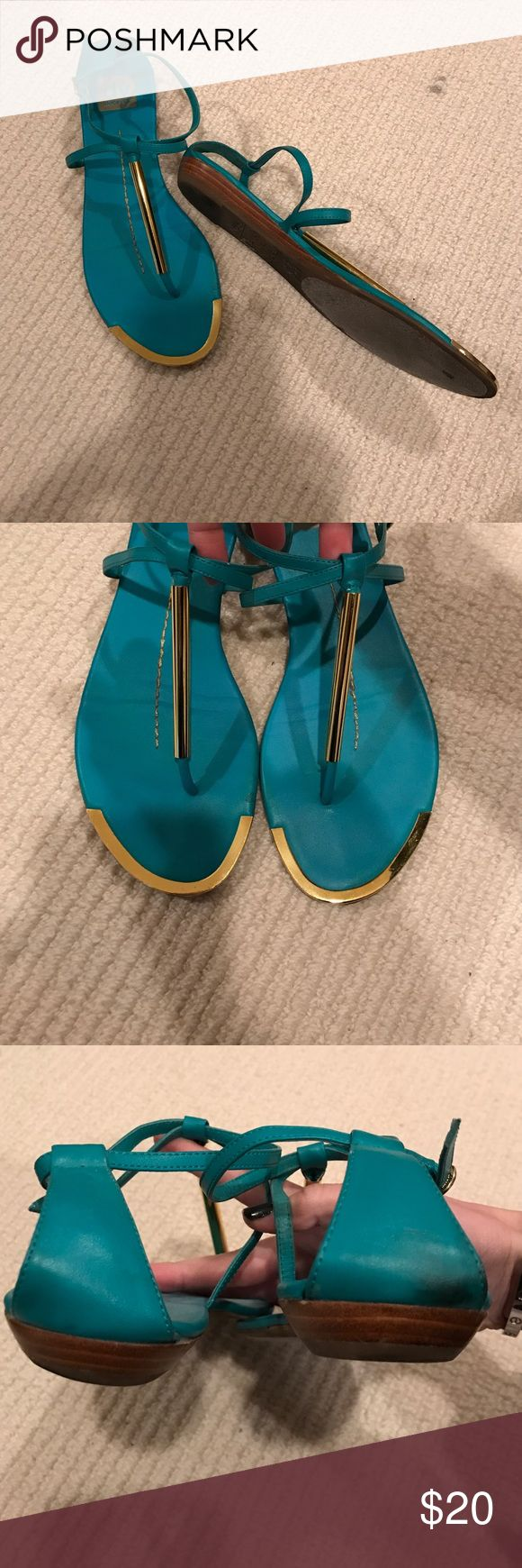 DV Dolce Vita turquoise sandals. Turquoise flat sandals. Gold hardware of T strap and around toe bed. Chris's cross detail around top of foot and ankle. Rubber soles with a 1/4 inch stacked wedge heal. DV by Dolce Vita Shoes Sandals