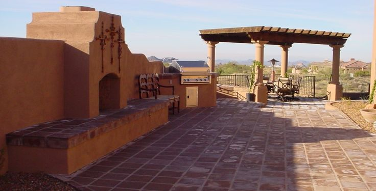 wonderful combination of this big outdooor fireplace's stucco color and the saltillo tile on the hearth and patio