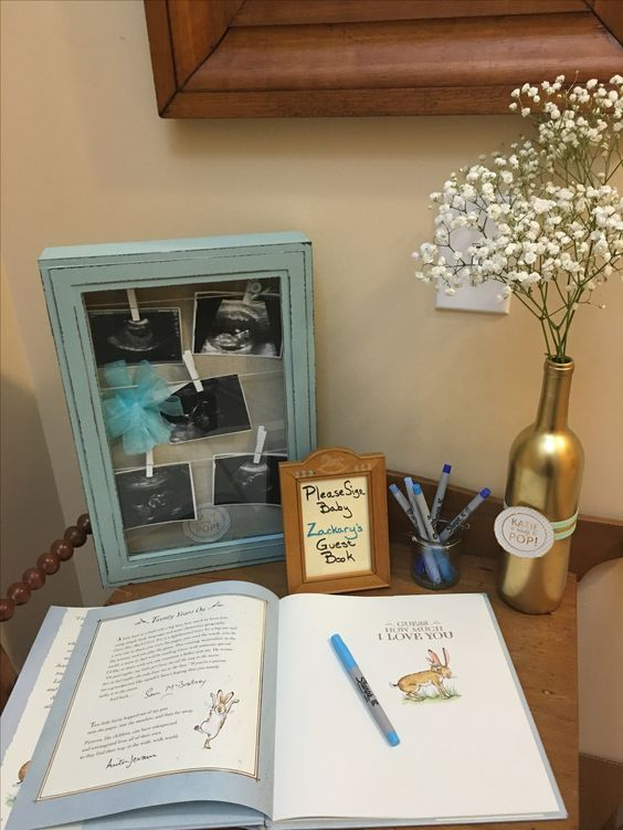 "Baby shower guest book and welcome table. Guests signed child's book, ""Guess How Much I Love You."" Ready to Pop baby shower themed gold painted wine bottle with mint and green ribbon and baby's breath and custom 'Katie Is Ready to Pop"" sticker. Ultrasound shadow box.:"