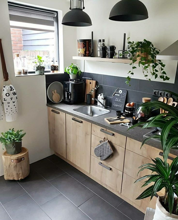 The kitchen of today – graphite coloured walls and workspace, offset by stark white, gleaming copper and lush green accents