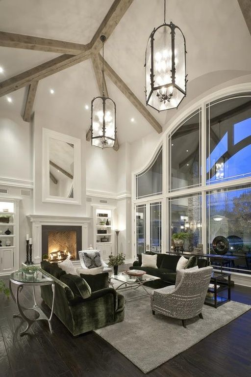 Soaring cathedral ceilings above dark wood floors. Enormous arching windows provide natural light. Traditional wood-burning fireplace topped by a massive mirror.