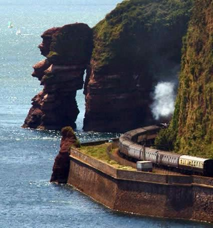 Devon, the line heading to Cornwall. Train rounding the cliffs, heading toward the Dawlish sea wall. One of the best train journeys in the uk. The tracks hug the estuary of the Exe river, then go along the edge of the beach for several miles. Must be an old pic~ thats a steam train. The cliffs are red from the high percentage of iron in the rock.
