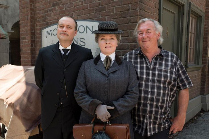 "David Hewlett (""Dilton Dilbert"") and Angela Vint (""Mildred Ash"") pose with Murdoch Mysteries showrunner Peter Mitchell during filming of Murdoch Mysteries episode ""The Accident""."