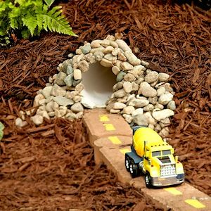 toy car tunnel in backyard play area.
