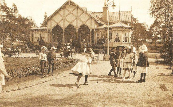 ENNEN WANHAAN KORKEASAARESSA Korkeasaaren eläintarha täytti tänä vuonna 125 v ja on yksi maailman vanhimmista eläintarhoista. Korkeasaaressa sijaitseva ravintola Pukki on valmistunut jo viisi vuotta aiemmin eli 1884. Tässä sen aikakauden tunnelmaa ravintola Pukin edustalta. Lapsilla on pallopeli kesken aikuisten nauttiessa aurinkoisesta päivästä kahvikupin äärellä.
