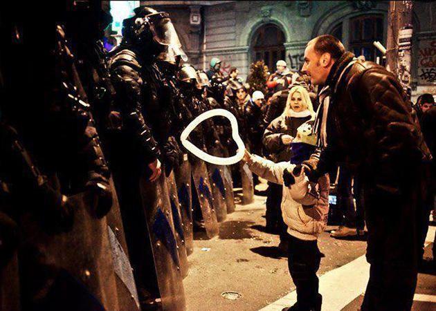 Un niño pequeño ofrece un globo con forma de corazón a un policía, Bucarest, 2012.  El agente tuvo el globo en la mano durante el resto de la manifestación.