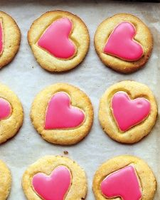 From Martha Stewart:  These crispy cornmeal cookies make the prettiest treat for Valentine's Day. A heart-shaped cookie cutter is pressed into each round just to create an impression. Once baked, the hearts are spread with pink glaze.