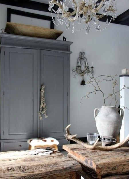 There is something so beautiful when a very rustic piece or two is combined with a simple elegance - chandelier & clean lines of the armoire. BellaRusticaDesign.com