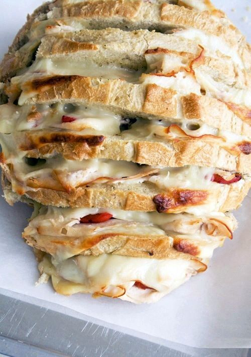 Store bought sour dough, slice then fill with fresh herbs, cheese and more. Drizzle with olive oil, garlic salt, and Parmesan. --- wrap in foil and bake at home or throw on the grill at a tailgate..