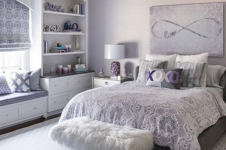 A built-in window seat adorned with purple and gray pillows is flanked by floor to ceiling built-in bookcases and dresser drawers.