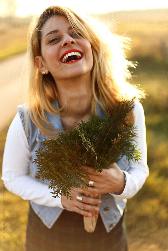 Outdoor portrait of a pretty young woman with green bouquet around sunset time.