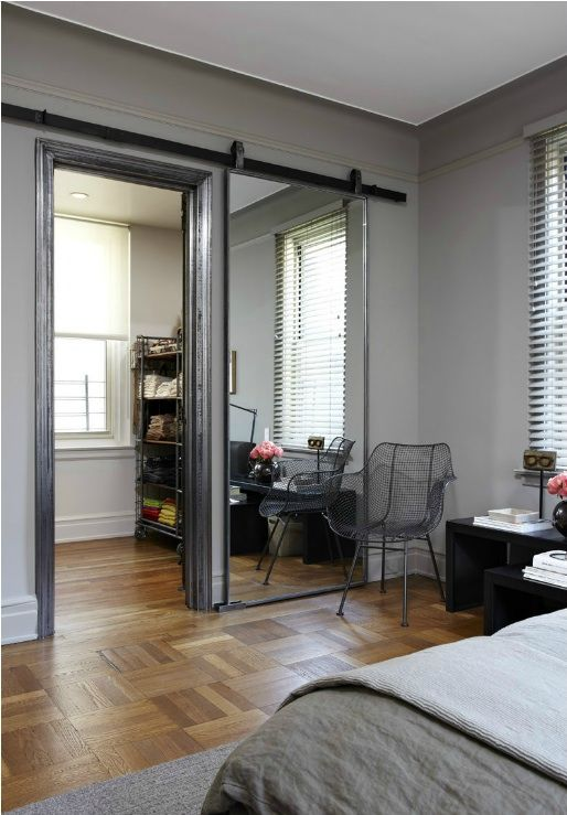 A Sliding Barn Door Mirror. Love this and it almost makes the room behind seem secret with the door closed.