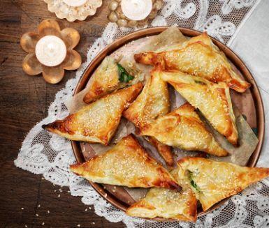 De här frasiga pirogerna fixar du enkelt med frysta smördegsplattor. Tina dem medan du fräser lök, vitlök, spenat och kryddor. Fyll plattorna och vik ihop till piroger som du strösslar med sesam och gräddar i ugnen.