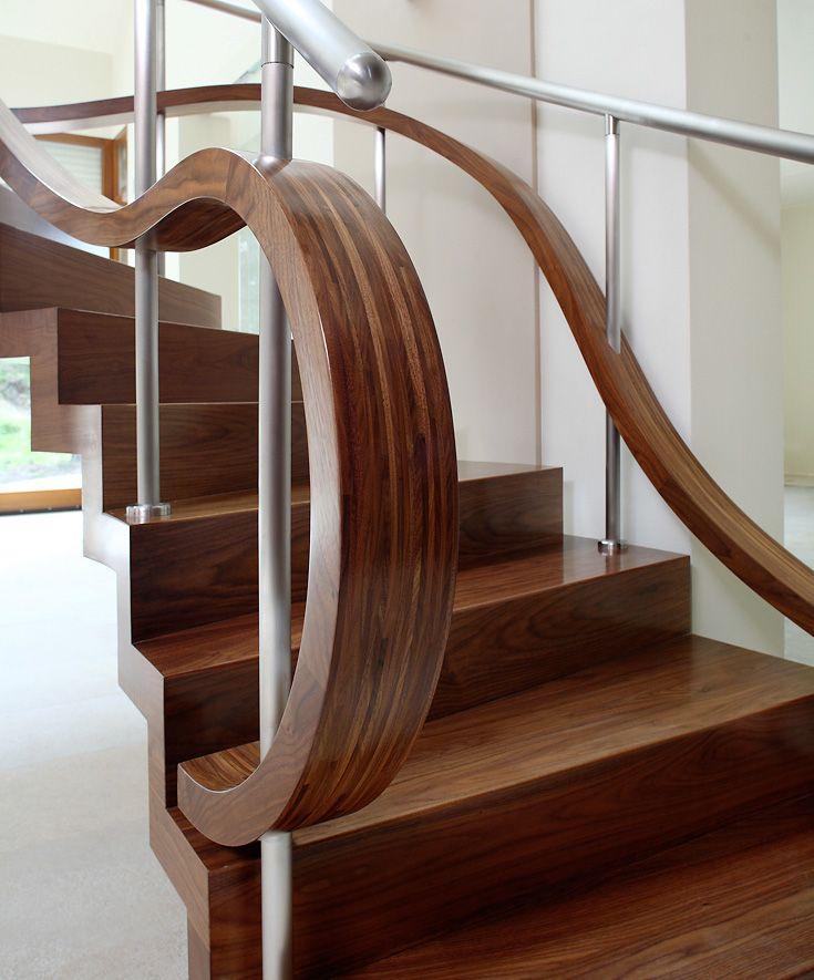 ST855 Łukowe schody dywanowe wykonane z orzecha amerykańskiego podwieszane na cięgnach ze stali szlachetnej. Balustrada obustronna ze stali szlachetnej z drewnianymi giętymi wstęgami. Realizacja wykonana w domu prywatnym , projekt – TRĄBCZYŃSKI