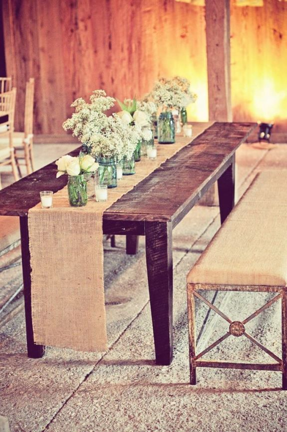 Rustic hessian table runners and jam jar flowers. Long table idea.