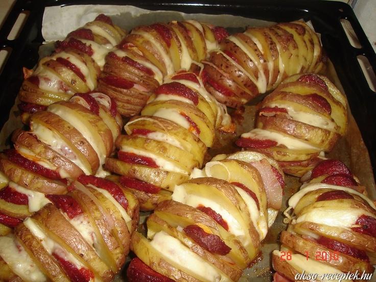 Töltött sült krumpli: Minden krumplit bevagdosunk keresztben 2-3mm vastag szeletekre (úgy, hogy a krumpli alja egyben maradjon). A krumplikat sütőpapírral bélelt tepsire rakjuk. Egy ecsettel a burgonyákat jól bekenjük sós étolajjal (olaj a vágásokba is befolyjon). 200 fokos sütőben puhára sütjük (kb 35-40 perc). A sütés vége felé a krumplik vágásaiba vékony sajtszeleteket, hagymakarikákat, szalonna- és sonkaszeleteket, kolbászkarikákat rakunk. Ezután még tíz percre visszatoljuk a sütőbe.