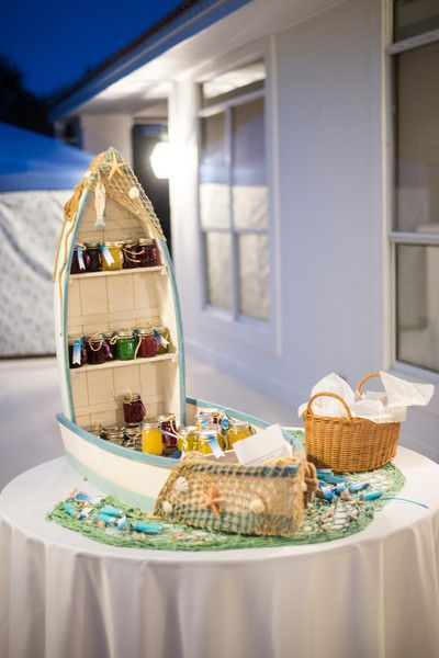Nautical-themed wedding favor display idea - homemade jam in boat + netting display {Cotton & Clover Photography}