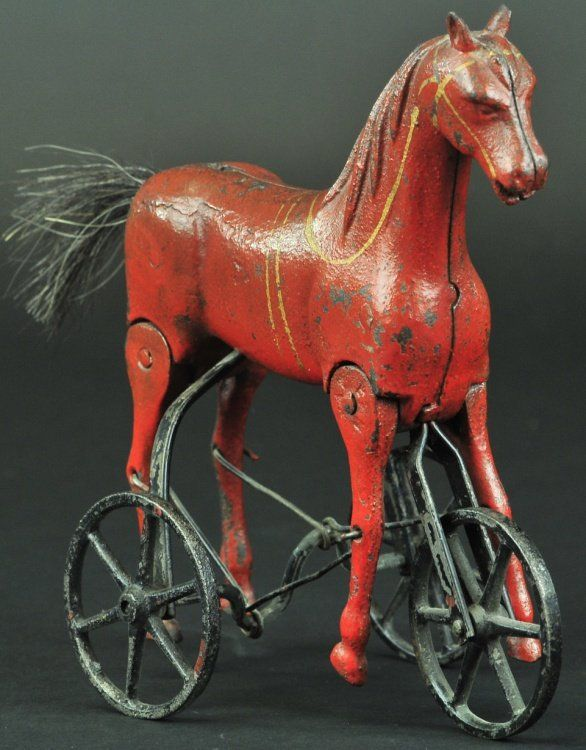 """Sold $2,500 c. 1890's, cast iron, scarce walking horse on three wheel version, painted in brown overall, this toy has a folk art quality to its design and molding effects, articulated action creates realistic walking motions. 7"""" l."""