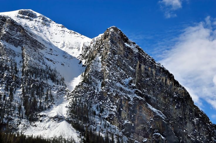 Sun Snow Summit - Close up shot of steep cliff mountain side with snowy canyon and blue sky background