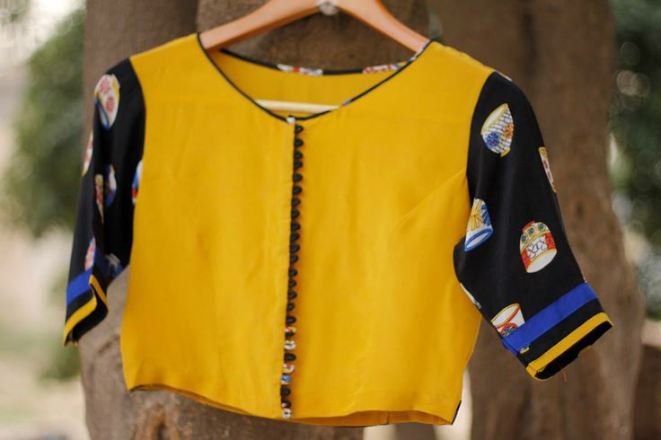 CR1311263 - Pure crepe blouse with jewel neck & loop placket design, front & back of the blouse are in yellow color, sleaves are in black color with digi print cup motif.