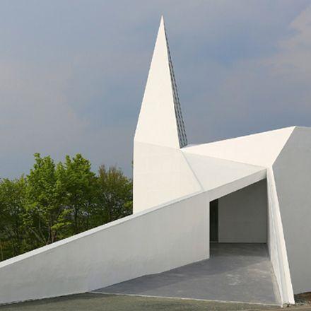 Die äußere Form ist abstrakt, signalisiert aber distanzlos direkt: Ich bin eine Kirche! Das von schneider + schumacher entworfene Gebäude feierte…
