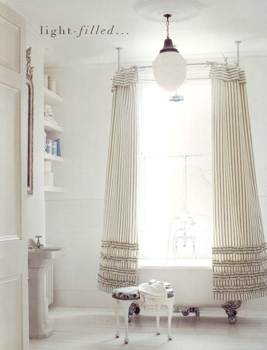 claw foot tub in front of the window.. That light is gorgeous!