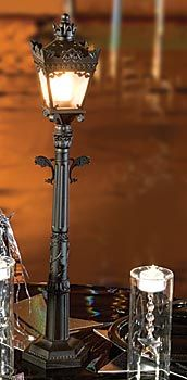 Mini City Street Lamp has the look of an ornate street light with it's wrought iron look and detailing. The electric mini street lamp measures 1 foot 10 inches high and is made of plastic.