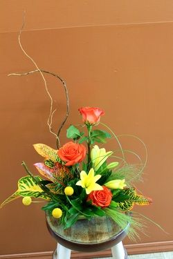 Yellow lilies, orange roses, craspedia, ornamental grass and tropical leaves.