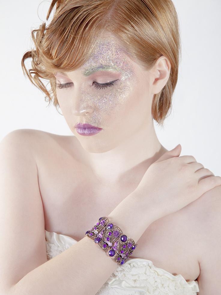 white dress; purple art deco bangle; purple lips; a lot of glitter; flamboyant hairstyle