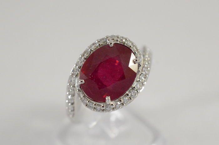Witgouden fantasie ring met een grote robijn omgeven door diamanten  De entourage ring is bezet met hoogwaardige geslepen diamanten. Exclusieve ring met een uniek design. De steen heeft een prachtige rode kleur. Smalle ring bezet met diamanten in de scheen en in een entourage om de robijn. De setting is prachtig opengewerkt.RobijnGewicht: Ca. 350 karaat Kleur: intense redMet natuurlijke insluitselsBehandeling: Colour and clarity enhancedTransparantie: gemiddeldAfmetingen: 10 - 8.0…