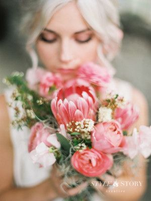 Wedding bouquet goals: a pink king protea flower surrounded by ranunculus, garden roses and pink peonies. | Style & Story Creative in Columbus, OH