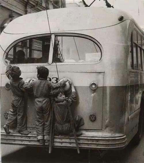 """Niños viajando de """"moscas"""", en la parte trasera de los añorados trolebuses de la Ciudad de México.  Foto tomada probablemente a mediados de los años 50's."""