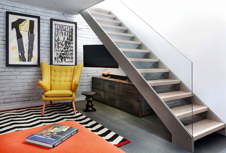 Lower level of the revamped London home with open tread glass and steel staircase and Papa Bear Chair in bright yellow London's Finest: High End Revamp of 70s Townhouse Leaves You Enthralled