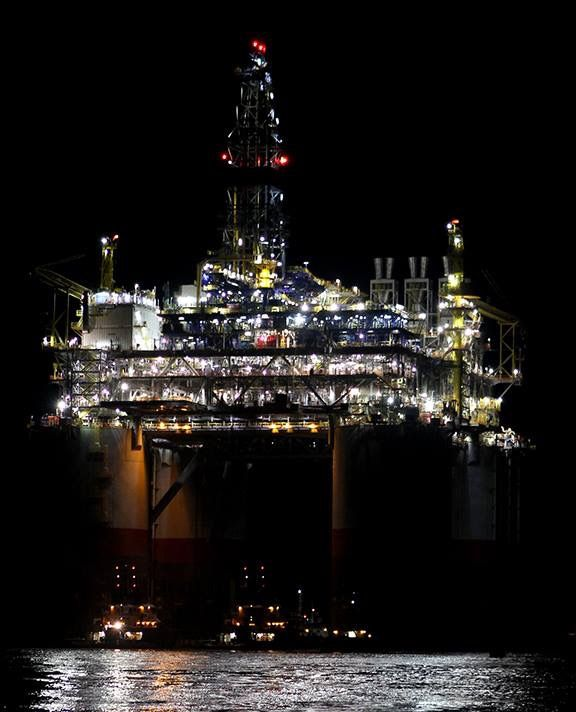 Offshore drilling & production rig going thru the ship channel at Port Aransas, Tx. In the early morning hours.